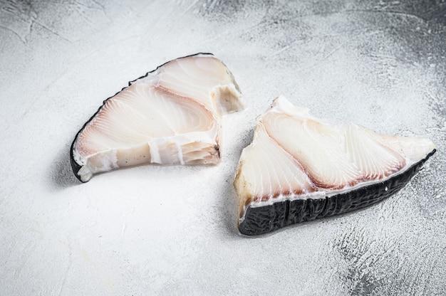 De ruwe lapjes vlees van haaienvissen op een keukentafel op wit. bovenaanzicht.
