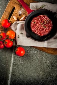 De ruwe organische koteletten van rundvleesburgers met kruiden op zwarte