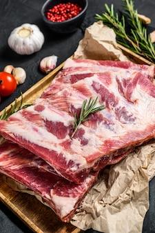 De ruwe ribben van het varkensvleesvlees met ingrediënten voor het koken van rozemarijn en knoflook in een houten kom. zwarte achtergrond. bovenaanzicht
