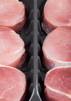 De ruwe ronde plakken van het varkensvleeslapje vlees in plastic dienbladcontainer op wit