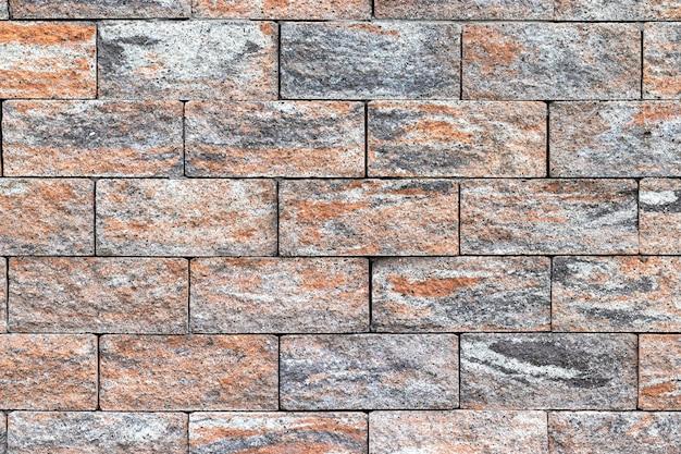 De ruwe textuur van de bakstenen omheining