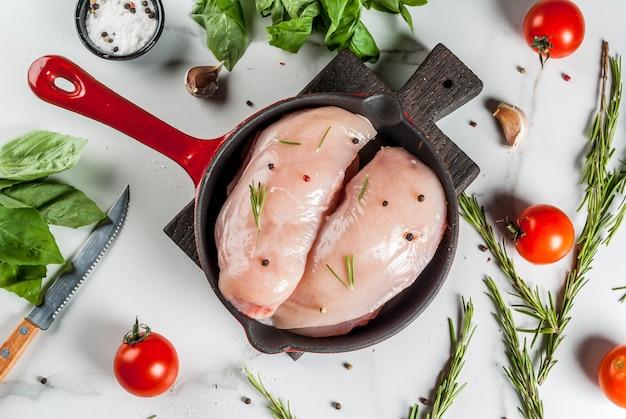De ruwe verse filet van de kippenborst met kruiden en kruiden voor het koken, in ijzer giet koekepan, witte marmeren lijst, exemplaar ruimte hoogste mening