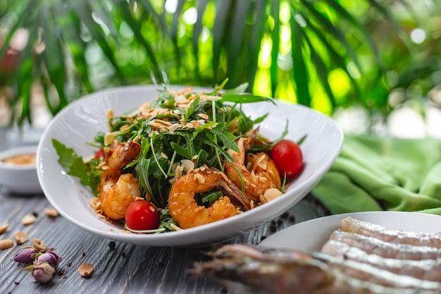 De salade geroosterde garnalen van zijaanzichtgarnalen met tomatenarugula en pinda op een plaat