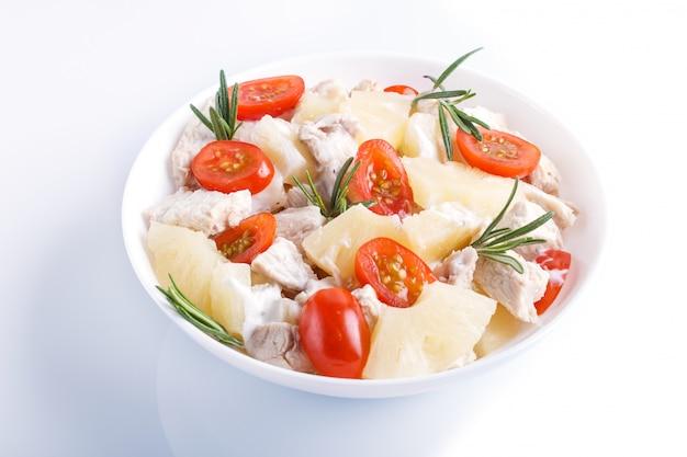 De salade van de kippenfilet met rozemarijnananas en kersentomaten op witte achtergrond worden geïsoleerd die