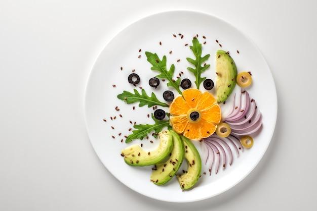 De salade van groenten en fruit is origineel versierd.