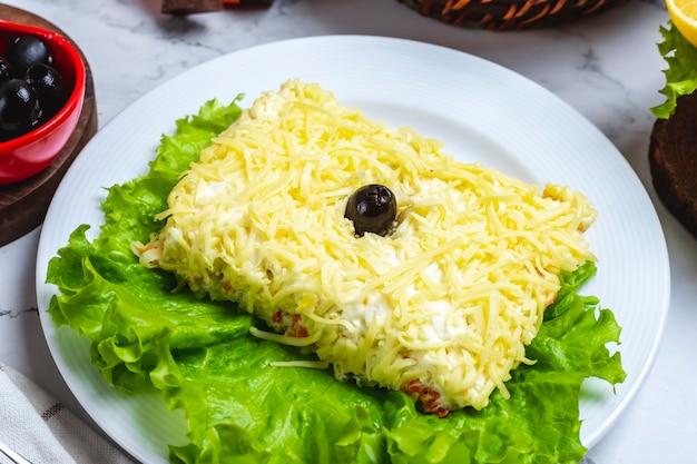 De salade van vooraanzichtmimosa op sla met zwarte olijven