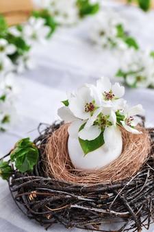 De samenstelling van de lentepasen van bloemen in een wit ei in een nest van takken op grijs tafelkleed.