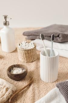 De samenstelling van de schoonheidsgezondheidszorg met oordopjes in rotankistje, handdoek, poeder, tandenborstels, vloeibare zeep op beige handdoek