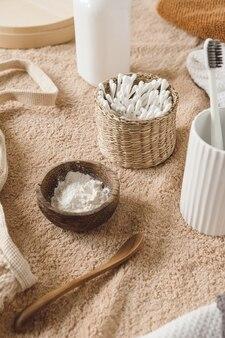 De samenstelling van de schoonheidsgezondheidszorg met oorstokken in rotankist, handdoek, poeder, tandenborstels op beige handdoek