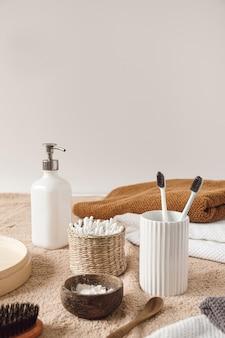 De samenstelling van de schoonheidsgezondheidszorg met oorstokken in rotankist, handdoek, vloeibare zeep, tandenborstels op beige handdoek