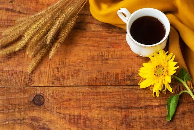 De samenstelling van de theekop van de herfst, gele sjaal, aartjes van tarwe en zonnebloembloem op een houten achtergrond