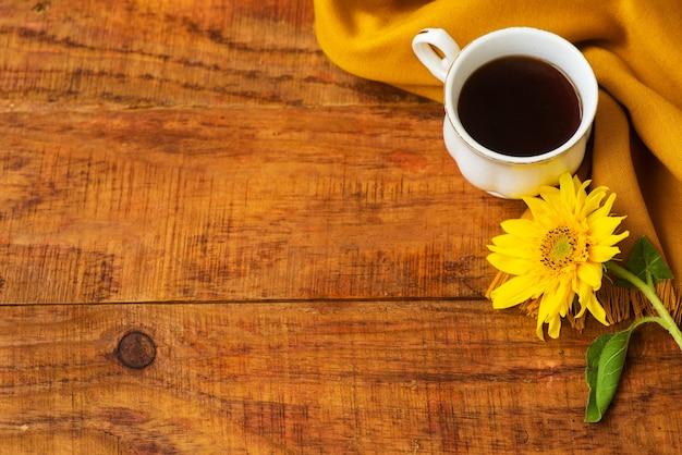 De samenstelling van de theekop van de herfst, gele sjaal en zonnebloembloem op een houten achtergrond