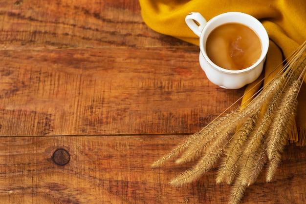De samenstelling van de theekop van de herfst met melk, gele sjaals en aartjes van tarwe op een houten ondergrond