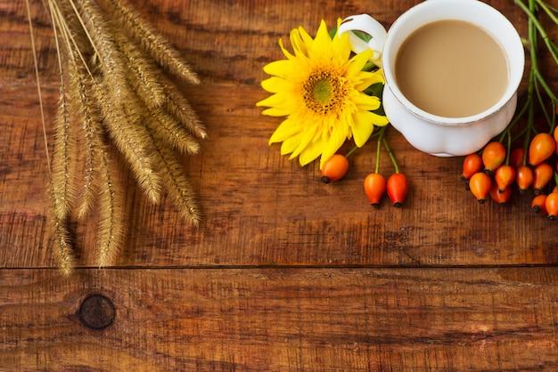 De samenstelling van de theekop van de herfst met melk, gele sjaals, zonnebloem, tarweaartjes en rozenbottel op een houten ondergrond