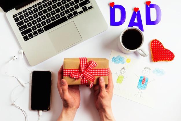 De samenstelling van de vadersdag met laptop en handen die huidig houden
