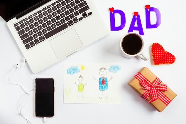 De samenstelling van de vadersdag met laptop en tekening