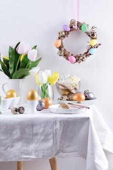 De samenstelling van de vakantiegelukwens van gediende lijst met met de hand gemaakte geschilderde eieren, gebakken koekjes, de verse bloemen van de lentetulpen en feestelijke kroon op een lichtgrijze muur. happy easter concept.