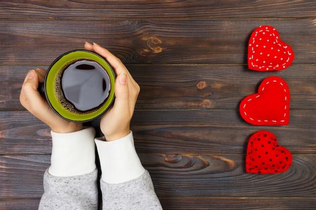 De samenstelling van de valentijnskaartendag met koffiekop en hart van rood fluweel. bovenaanzicht. ruimte kopiëren