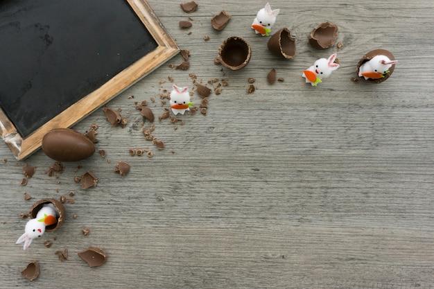 De samenstelling van pasen met een schone lei, chocolade-eieren en decoratieve konijnen