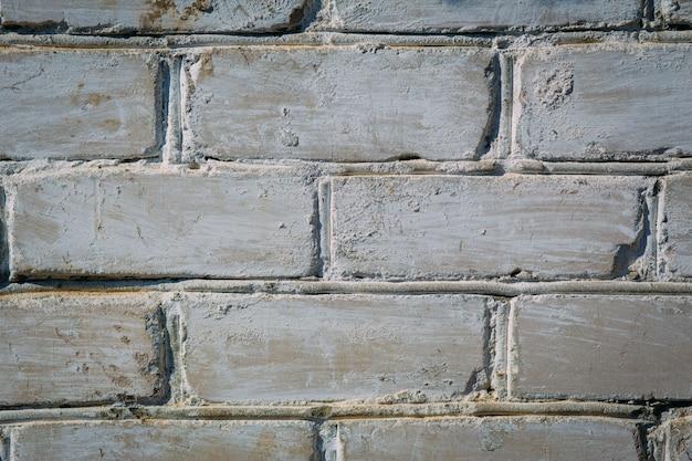 De samenvatting doorstane textuur bevlekte oude lichtgrijze en oude verf witte bakstenen muurachtergrond van de gipspleister