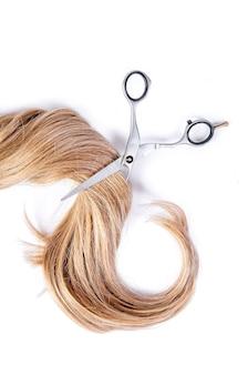 De schaar van de kapper met bundel van blond haar op een wit