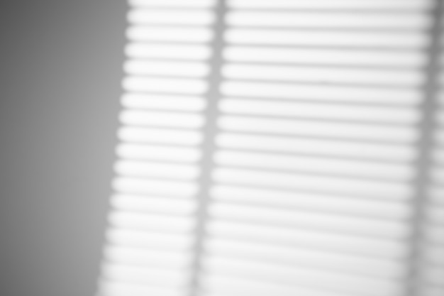 De schaduw van de jaloezieën van het raam op een witte muur bij zonnig weer met fel licht. schaduwoverlay-effect voor foto.