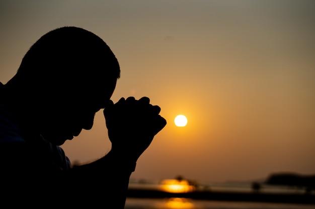 De schaduw van de man die bidt en denkt