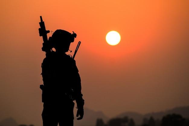 De schaduw van een soldaat op het slagveld patrouilleren bij zonsondergang