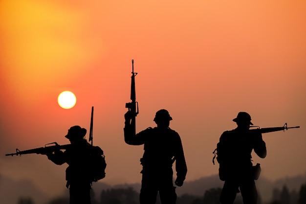 De schaduw van soldaten op het slagveld die bij zonsondergang patrouilleren