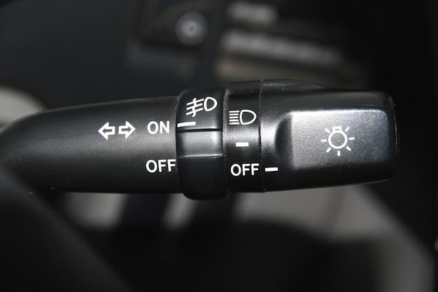 De schakelaar van draai en licht van koplampen van de auto op een wiel