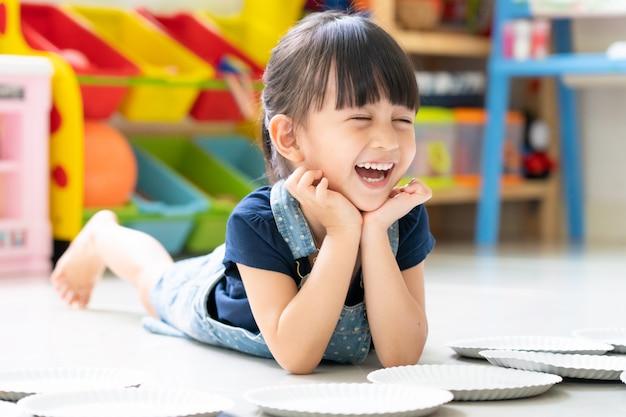 De schattige 3-jarige lacht met een volledig geluksmoment terwijl ze binnenshuis speelt.