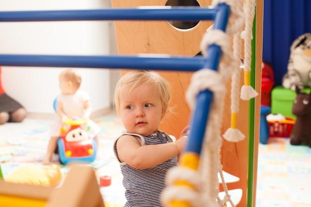 De schattige baby die op de speelplaats op de kleuterschool speelt