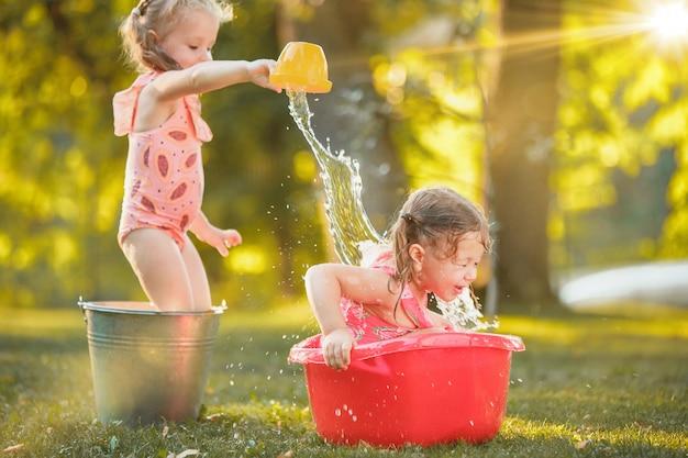 De schattige kleine blonde meisjes spelen met water spatten op het veld in de zomer