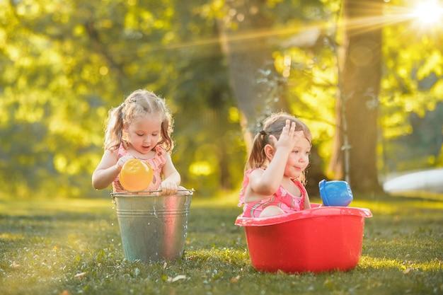 De schattige kleine blonde meisjes spelen met waterspatten op het veld in de zomer