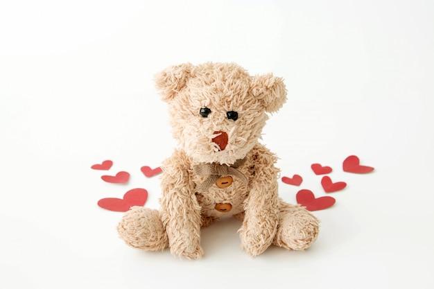 De schattige kleine teddybeer is zo blij met veel harten in valentijn.