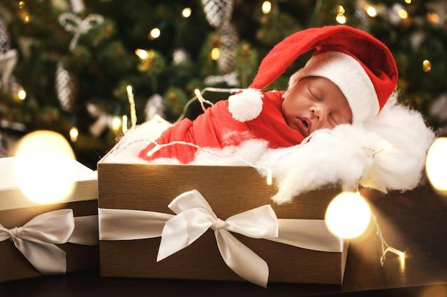 De schattige pasgeboren baby die de hoed van de kerstman draagt slaapt in de doos van de kerstmisgift