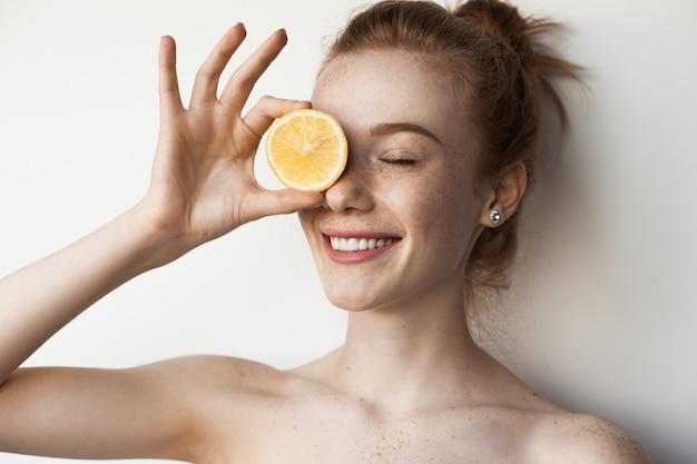 De schattige vrouw met sproeten met gemberhaar bedekt haar oog met een citroen op een witte muur