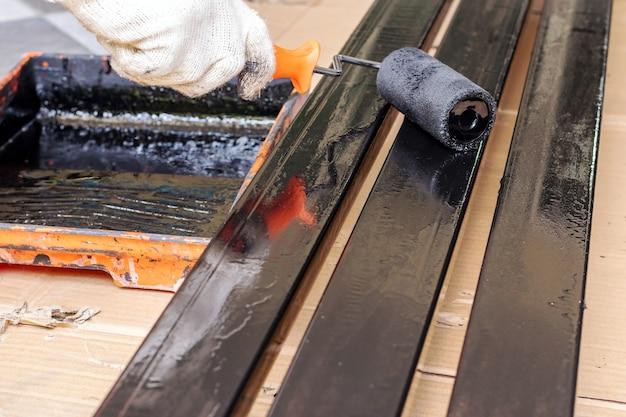 De schilder draagt stoffen handschoenen en gebruikt een zwarte verfroller op de stalen staaf.