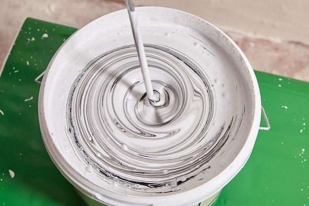 De schilder gebruikt een elektrische mixer om zwarte en witte verf te mengen om een grijze kleur te creëren.