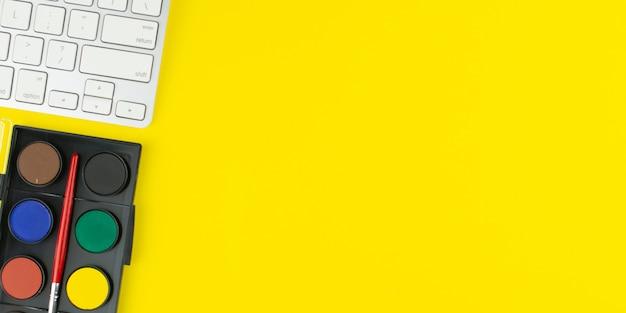 De schilder kleurt palet en toetsenbord op gele achtergrond.