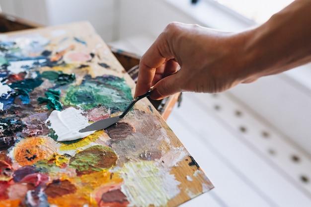 De schilder overhandigt dicht omhoog mengt verven
