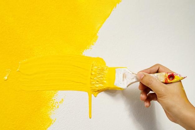 De schilder schildert de muren in geel met het interieur van de huiskamer.