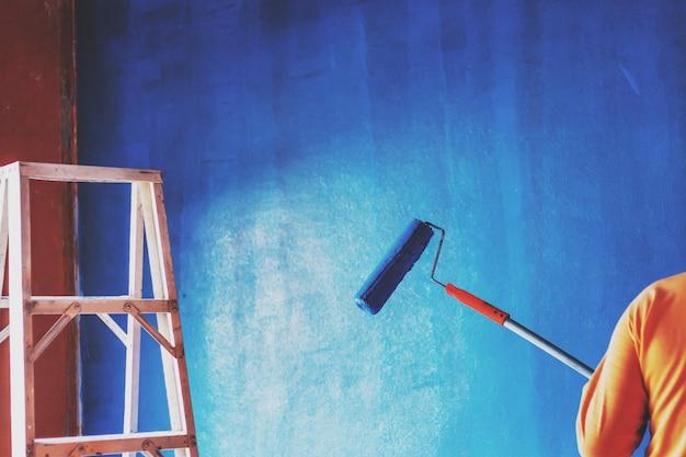 De schilder schildert de muur met een vachtroller, een achtergrond, een achtergrond
