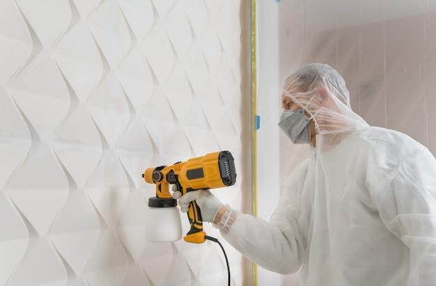 De schilder schildert een 3d muur met een spuitpistool.