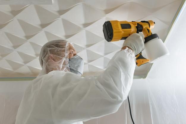 De schilder schildert een 3d plafond met een spuitpistool.
