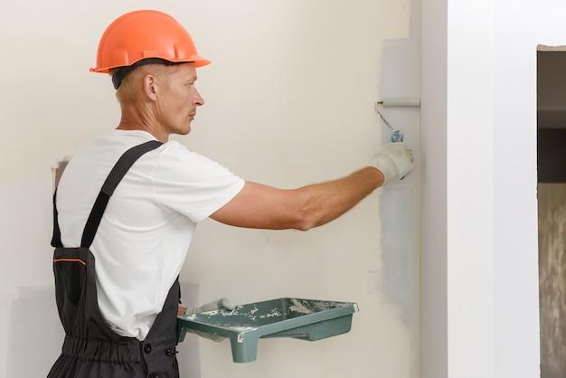 De schilder schildert een muur in een kamer met een roller.