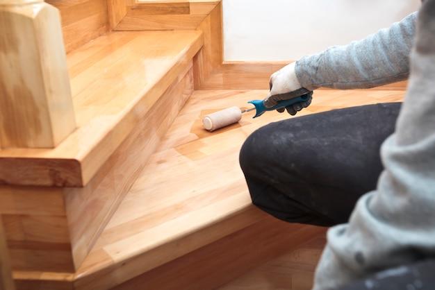 De schilder schildert een vernis houten plank met roller