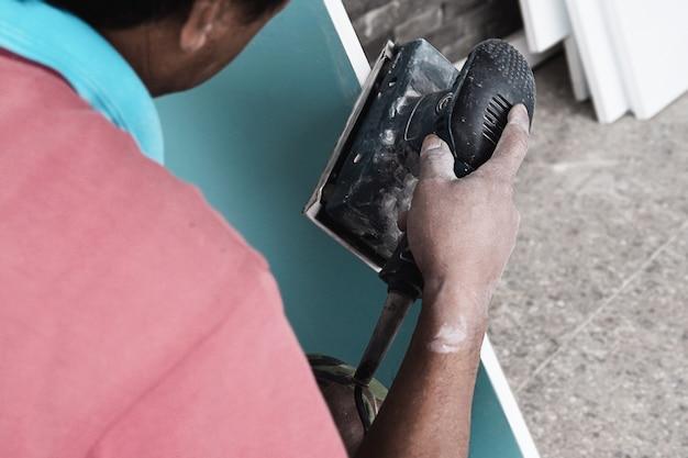De schilder werkt aan het proces van het schilderen van meubels met behulp van een scrubmachine