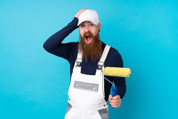 De schildersmens met lange baard over geïsoleerde blauwe muur verrast en richtend vinger aan de kant