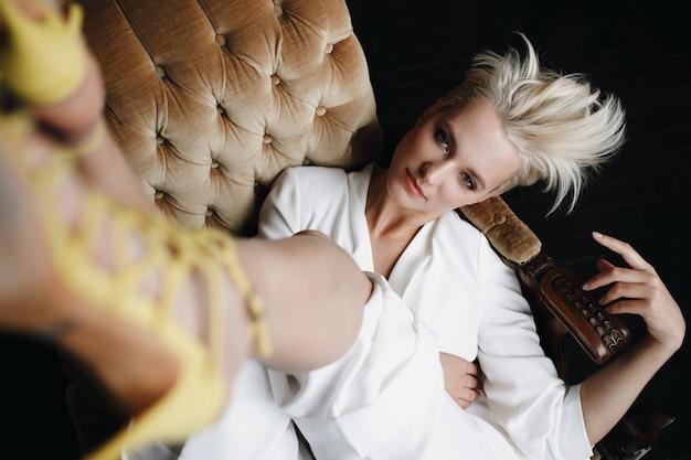 De schitterende blonde mannequin in witte reeks zit op een zachte leunstoel die haar benen tegenhoudt